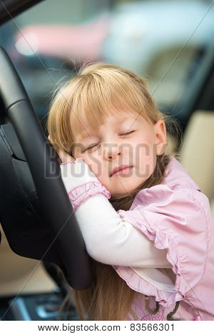 Little girl sleeping on car steering wheel