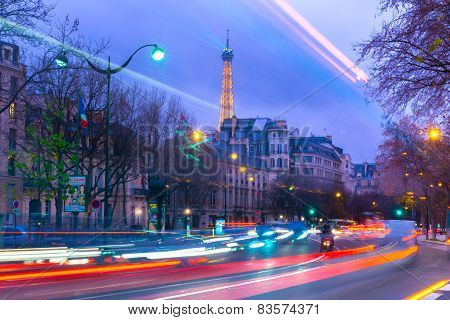 Cityscape with the shimmering Eiffel Tower and night street in Paris, France