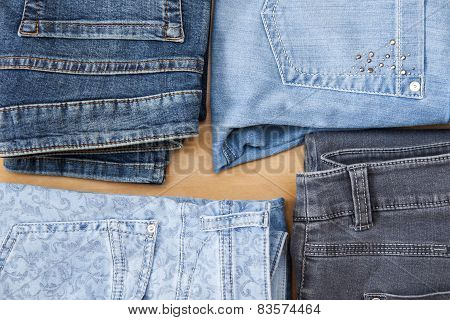 Jeans of various colors on a counter in shop, the top view