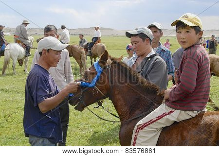 Men attach blue ribbon to the bridle of winner's horse circa Harhorin, Mongolia.