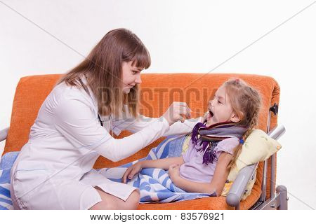 Pediatrician Looks At The Throat Of A Sick Child