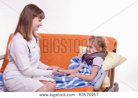 Pediatrician Looks At The Sick Child And Keeps His Hand