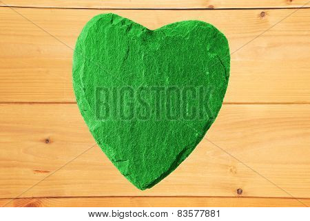Green Heart With Slate Structure And Wooden Background
