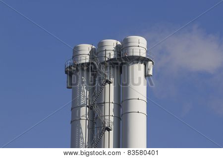 triple tube emits smoke against the blue sky