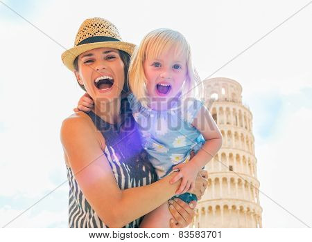 Portrait Of Smiling Mother And Baby Girl In Front Of Leaning Tow