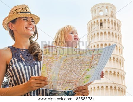 Happy Mother And Baby Girl With Map Looking Into Distance In Fro