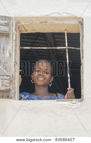 THIAROYE, SENEGAL, AFRICA - JULY 18, 2014 - Young woman standing at the window of her house
