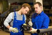 stock photo of angles  - instructor teaches steel construction trainee how to use an angle grinder - JPG