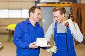 stock photo of inspection  - Two steel construction workers with angle grinder inspecting metal pieces - JPG