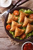 picture of samosa  - samosa on a plate with sauce and tomatoes closeup - JPG