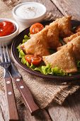 pic of samosa  - vegetarian samosas on a plate with tomatoes and lettuce on a wooden table - JPG