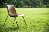 image of lawn chair  - old plastic chair with stainless support on green lawn - JPG