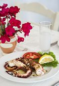 foto of octopus  - grilled octopus with glass of ouzo in restaurant - JPG