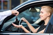 foto of car keys  - Car dealer giving keys of a new car to happy smiling woman. Concept for car rental