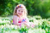 stock photo of bunny rabbit  - Adorable little girl cute curly toddler in a colorful summer dress playing with a real rabbit having fun with her pet bunny in a beautiful garden with first spring snowdrop flowers - JPG