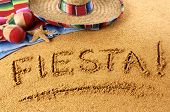 stock photo of mexican fiesta  - The word Fiesta written in sand on a Mexican beach with sombrero straw hat traditional serape blanket starfish and maracas - JPG