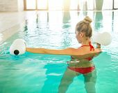 stock photo of health center  - Blond young woman doing aqua aerobics with foam dumbbells in swimming pool at the leisure centre - JPG