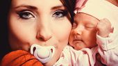 pic of nipple  - Parenting and love concept. Closeup funny mother with nipple in her mouth hugging one month old baby girl closeup portrait