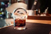 stock photo of marsala  - Black russian cocktail on the bar stand on rubber mat. Shallow DOF and marsala tonned ** Note: Visible grain at 100%, best at smaller sizes - JPG