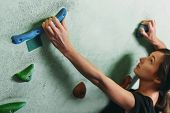 image of climb up  - Young woman climbing up on rock wall in gym close - JPG