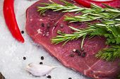 stock photo of beef shank  - Fresh beef steak on board with aromatic spices on a wooden background - JPG