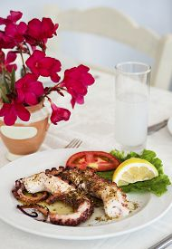 picture of ouzo  - grilled octopus with glass of ouzo in restaurant - JPG