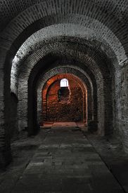 image of dungeon  - A dark dungeon tunnel with a small window at the far end