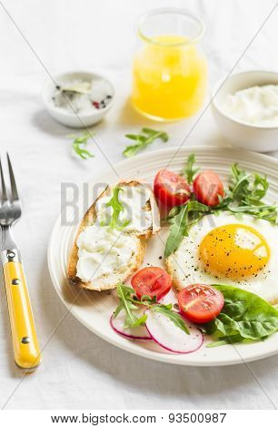 Fried Egg, Vegetable Salad And A Grilled Cheese Sandwich On A Light Background