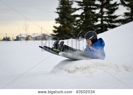Winter Fun - Child Sledding/Tobogganing Fast Over Snow Ramp
