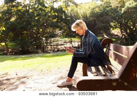 mid age woman using smart phone at the park sitting on a bench