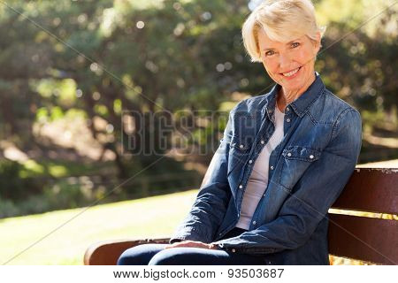 attractive senior woman sitting on a bench outdoors