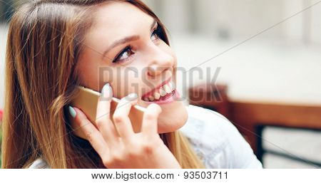 Close up Smiling Pretty Young Woman Talking to SOmeone on Mobile Phone While Drinking at the Cafe