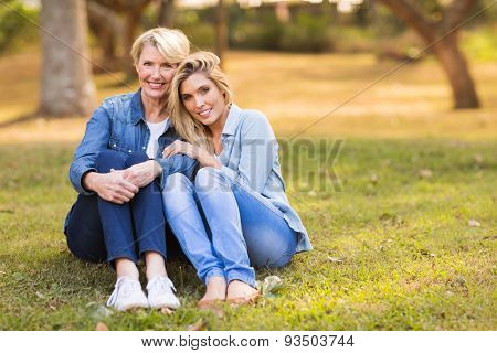 happy mid age mother and daughter sitting on grass in the park