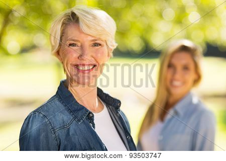 portrait of middle aged woman in front of young daughter outdoors