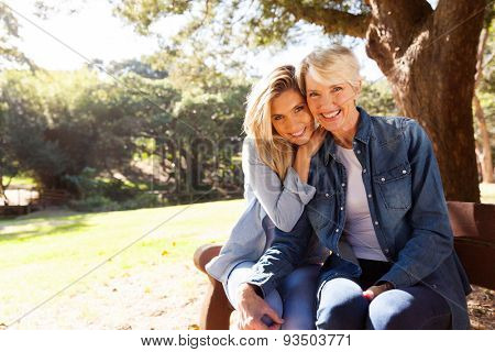 attractive mid age mother and daughter sitting on a bench outdoors