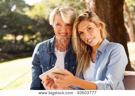 portrait of pretty mother and daughter using smart phone in the park
