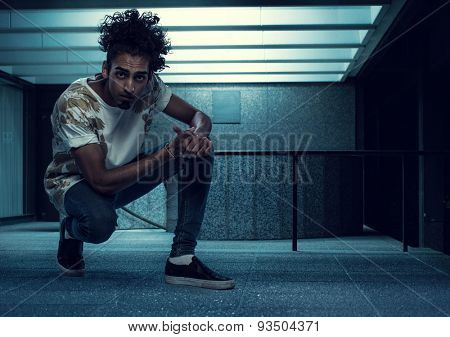 Curly-Haired Young Handsome Guy Squatting Inside an Empty Building and Looking at the Camera.