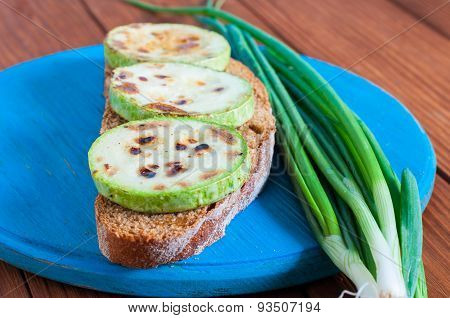 Open Sandwich With Butter, Grilled Vegetable Marrow And Green Onion In Rural Or Rustic Kitchen At Vi