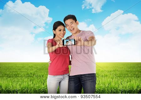 Asian Couple Doing Selfie On Meadow