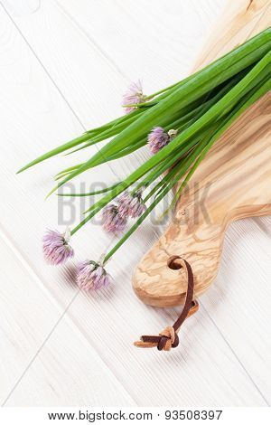 Fresh spring onion on cutting board over white wooden table