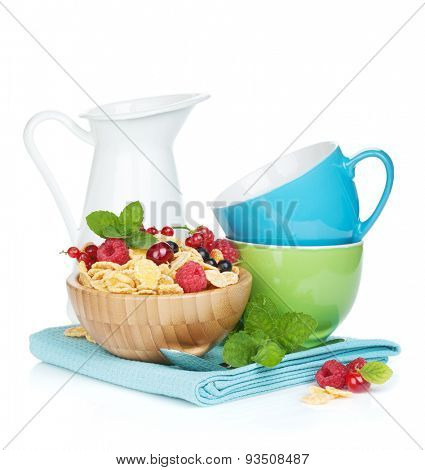 Fresh corn flakes with berries, milk jug and cups. Isolated on white background
