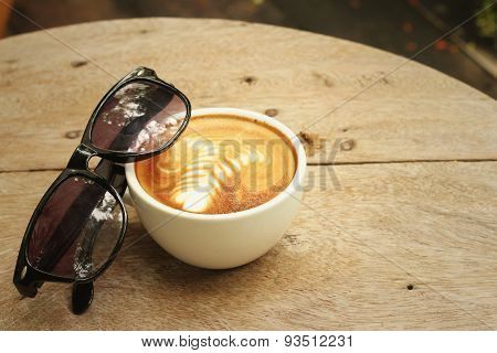 Coffee With Sunglasses On Background Of Wooden.