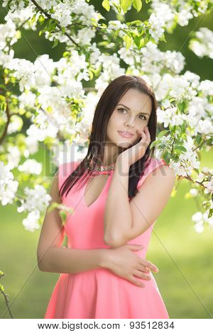 Young spring fashion woman. Trendy girl in the flowering trees in the spring summer garden. Springtime or summertime. Lady in spring landscape background. Allergic to pollen of flowers.Spring allergy
