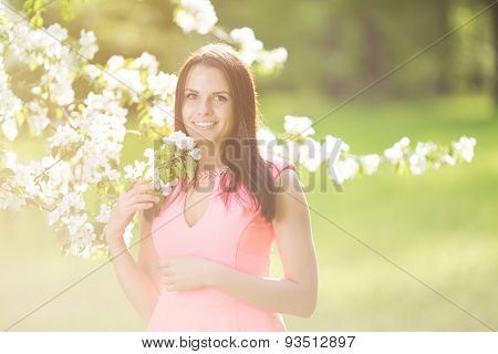 Young spring fashion woman. Trendy girl in the flowering trees in the spring summer garden. Springtime or summertime. Lady in spring landscape background. Allergic to pollen of flowers. Spring allergy