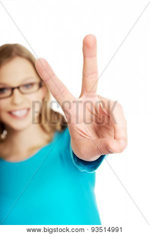 Teenage woman showing victory sign