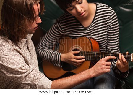 Young Musician Teaches Female Student To Play The Guitar