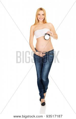 Happy pregnant woman with alarm clock expecting baby
