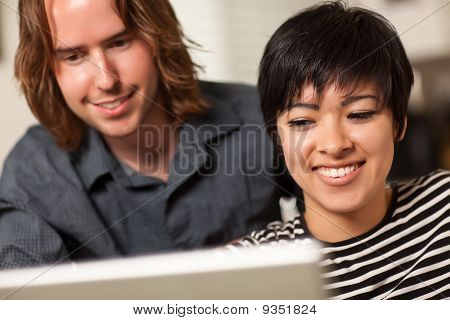 Happy Young Man And Woman Using Laptop Together