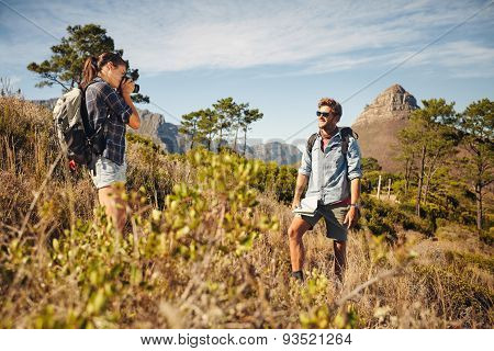 Woman Taking A Picture Of Boyfriend Outdoors In Nature