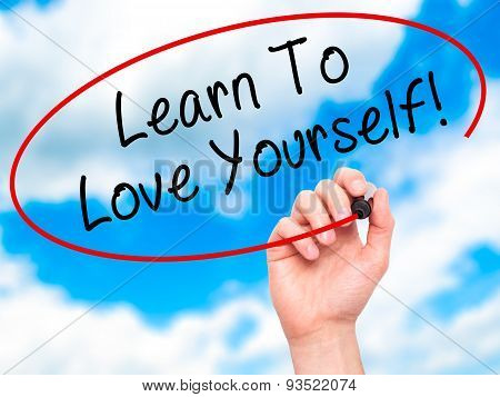 Man Hand writing Learn To Love Yourself with marker on transparent wipe board.